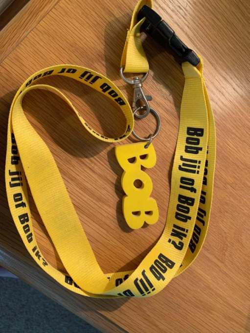 """The word Bob in yellow letters attached to a yellow lanyard, on which is written: """"Bob jij of Bob ik?"""" It was from a Dutch drink/driving campaign."""