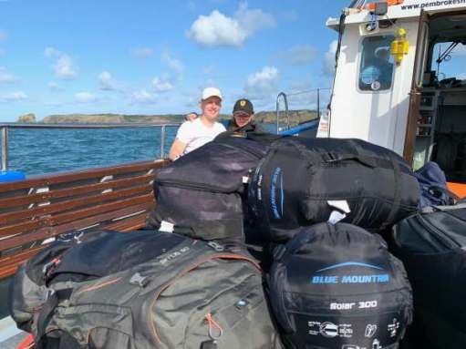 The two Sams posing on the boat behind the pile of luggage. Skomer is visible behind them.