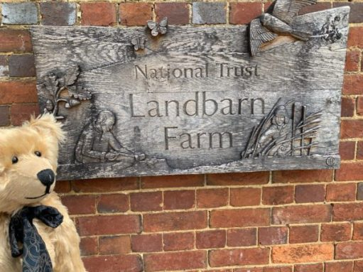 "A beautifully carved wooden sign saying ""National Trust Landbarn Farm""."