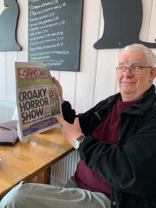 Bobby in the Black Caat café in Worthing, holding up a copy of the Sun newspaper.