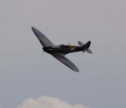 Spitfire flying in an almost cloudless sky.