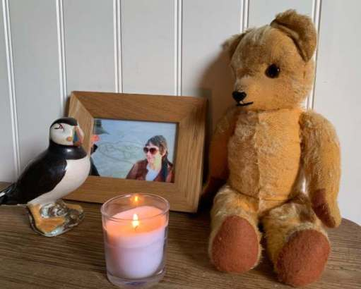 Eamonn in Laurel Cottage with a photo of Diddley, a Puffin - and a lit candle.