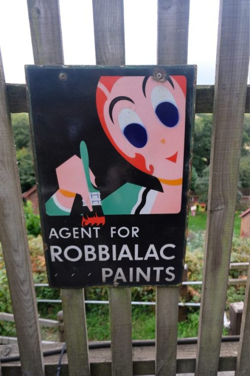 "West Somerset Railway - Enamel Sign ""Agent for Robbialac Paints"" attached to a station fence."