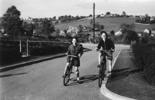 A boy (Chris), and a girl (his sister Elizabeth) in Brownie Uniform, both on bikes, but stopped at the top of a short hill. Chris is on the ex Paratrooper's Bicycle.