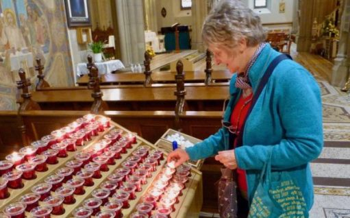 Angie placing the second candle. One for Jim & Rose, her parents and the second for Di. St Eunan's Cathedral, Letterkenny, Donegal on 7 June 2019.