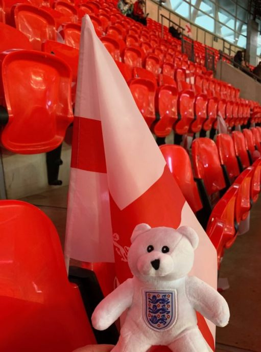 Ellen (a white bear with the England logo on her chest) and a free England flag in the seats at a near-empty Wembley Stadium.