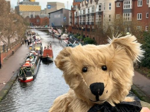 Bertie on a bridge over the canal, with the boats of the Birmingham Floating Christmas Market behind.