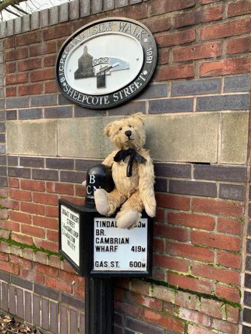 "Bertie sat on a canal milepost underneath another sign that says ""Canalside Walk Sheepcote Street"""