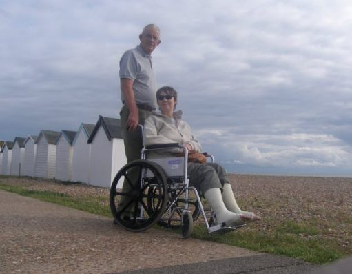 Bobby pushing Diddley (who has both ankles in plaster) in a wheelchair along Goring-by-Sea seafront, behind som ewhite beach huts.