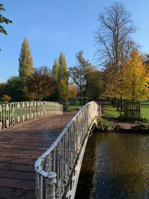 Looking across an iron bridge over the river in Morden Hall Park.