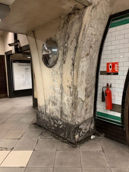 Pillar within Tooting Broadway station showing signs of damp in the plaster.