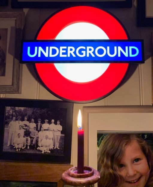 Lighting a Candle to Diddley. Underground illuminated roundel, family pictures and a lit candle.