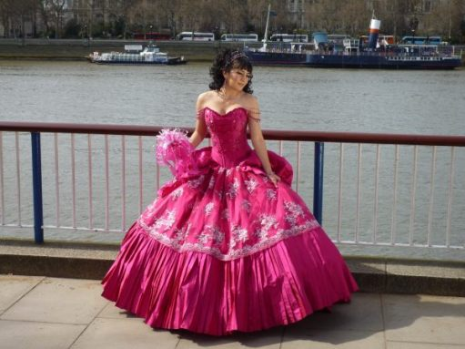 Lady in a posh pink dress, fanning out around the feet. The Thames is in the background.