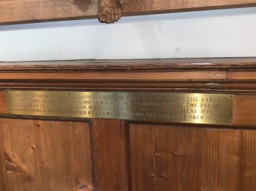 The brass plaque underneath the carving.