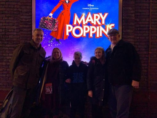 The Ball Family in front of an illuminated Mary Poppins poster.
