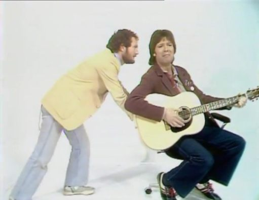 Cliff Richard playing guitar sitting on a typists chaier, with Kenny Everett wheeling him away...