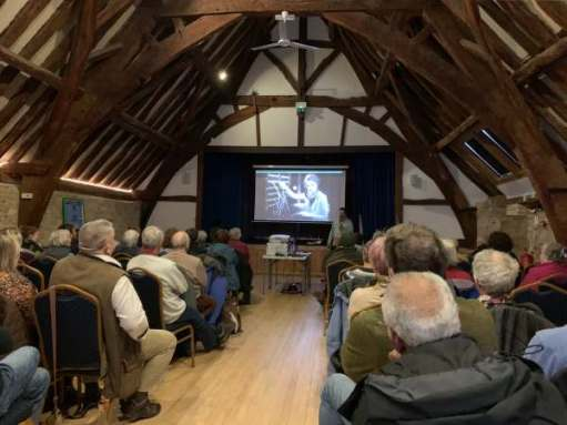 Interior of the Tithe Barn at Bishop's Cleeve. A polished wooden floor underneath an arched roof. A video presentation is being played on a screen on the front wall.