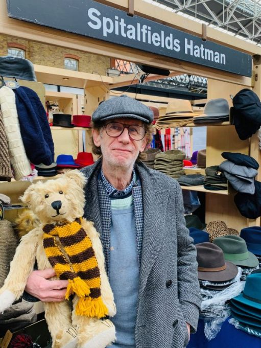 Bertie, wearing his Sutton United scarf, being held by the Spitalfields Hat Man, who is wearing a flat cap.