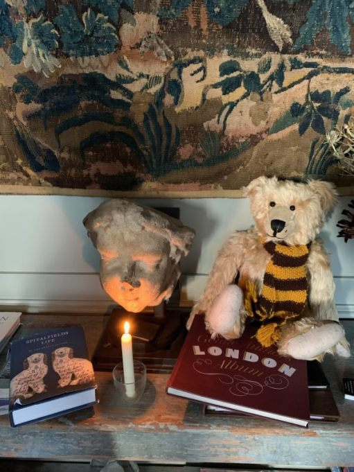 Candle lit for Diddley on top of a cupboard. There are some books on top, a gargoyle behind, and Bertie, wearing his Sutton United scarf. to the side.