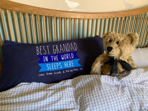 "Bertie in a double bed alongside a pillow that reads ""Best Grandad in the World sleeps here Love from Giselle and Daisy-Mae xx"""