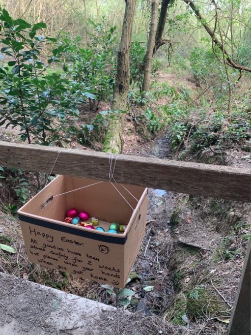 """A box, hanging from a wooden fence, containing Easter Eggs, with a note saying """"Happy Easter""""."""