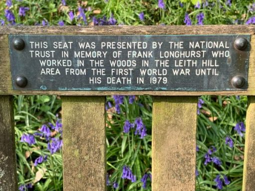 """Plaque on the seat that reads """"This seat was presented by the National Trust in moemory of Frank Longhurst who worked in the woods in the Leith Hill area from the First World War until his death in 1979""""."""