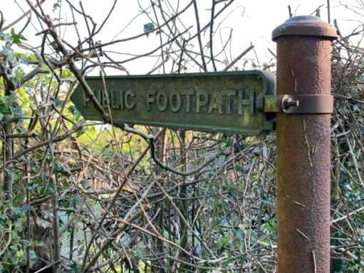 """A rusty old metal """"Public Footpath"""" sign, almost buried in the overgrowth."""