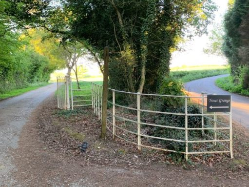 """Sign pointing off the narrow country lane to """"Trout Grange"""". A private estate with a Public footpath."""