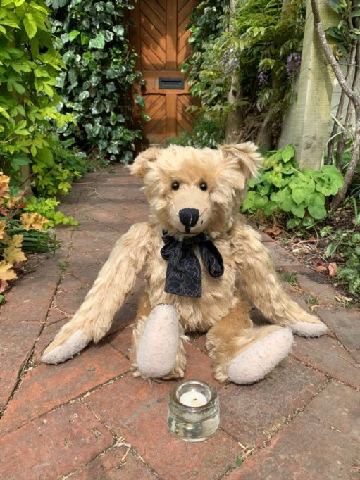 Bertie sat on the herringbone path with a lit candle for Diddley in front of him.
