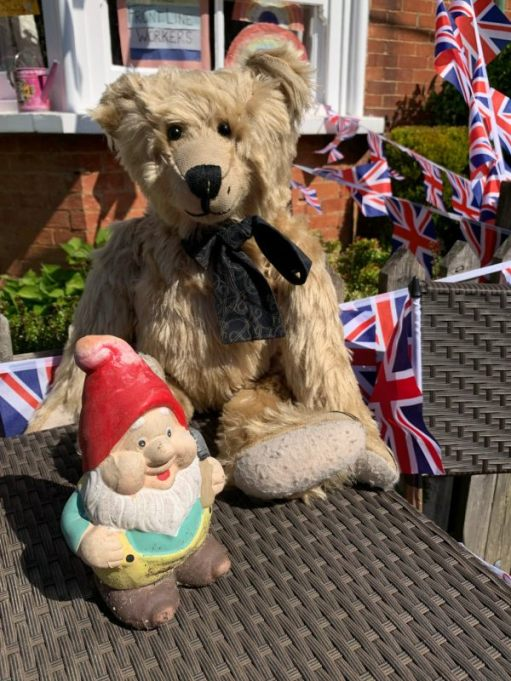 Bertie sat on a table in the garden of Laurel Cottage, with a garden gnome.
