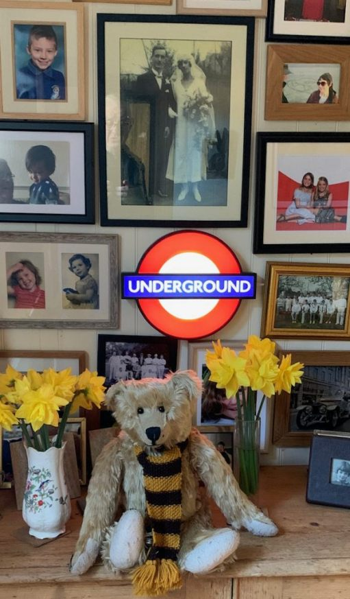 Bertie in front of an illuminated Underground roundel, a picture of Bobby's parents and other memorabilia.