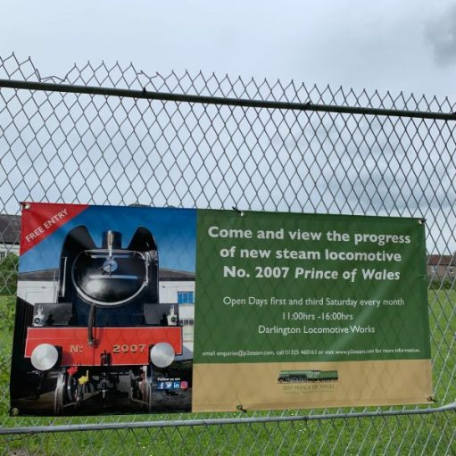 Banner on the fence outside Darlington Locomotive Works advertising another brand new steam engine under construction. 2007 Prince of Wales. P2 Class.
