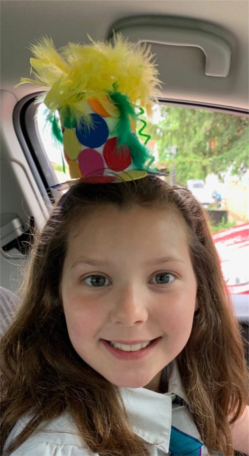 Kyla in a car, wearing a party hat.