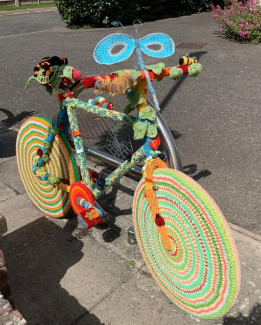 Yarnbomb Sisters - knitted bicycle with wheel rims in multi-coloured concentric circles and a butterfly on the handlebars.
