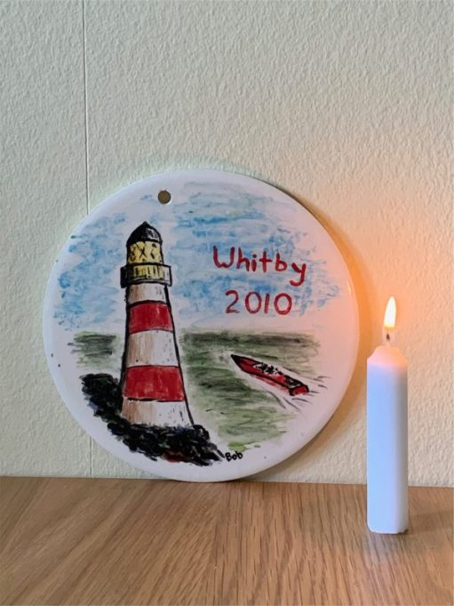 And here is that plaque painted on a rainy day in Whitby ten years ago, behind a candle lit for Diddley.