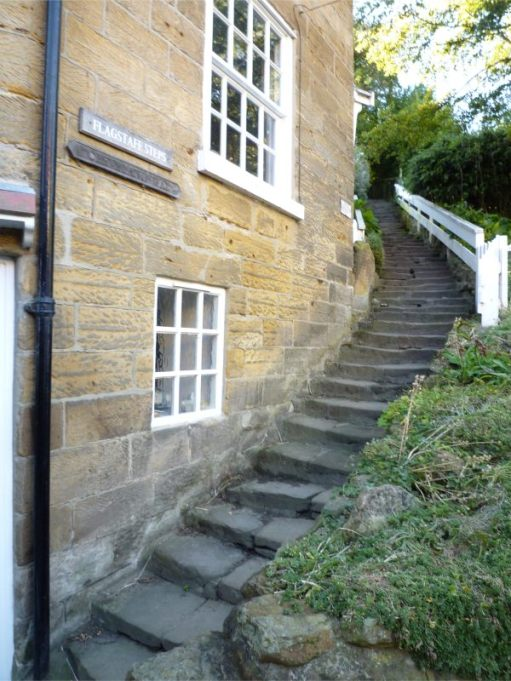 Steep steps of the Cleveland Way up the side of a stone built house.