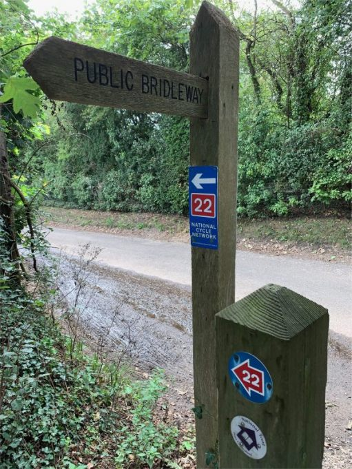 Signpost for a Public Bridleway, with more waymarker signs on it.