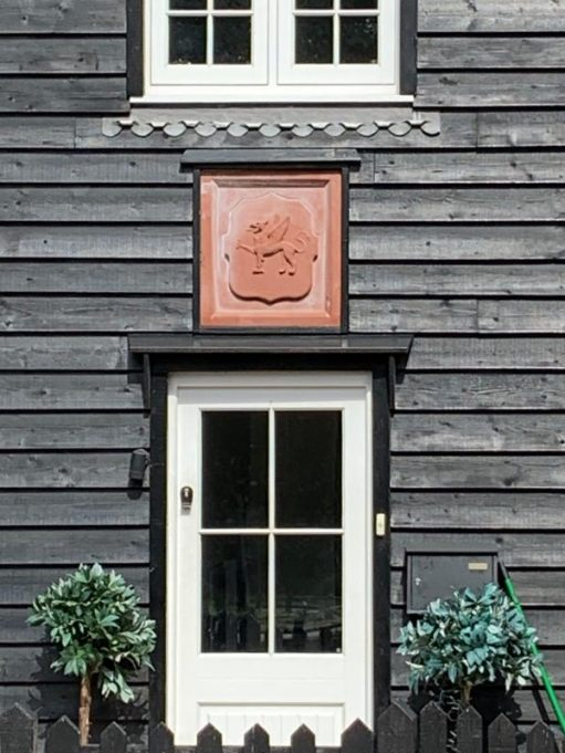 Griffon above a door on a wooden building.