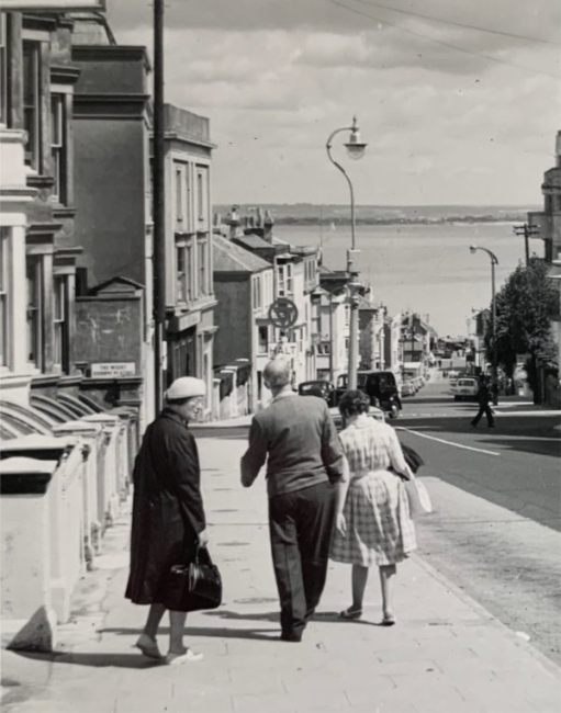 Black & White photograph looking at Bobby's parents walking down the hill towards the Solent. His father's limp is obvious.