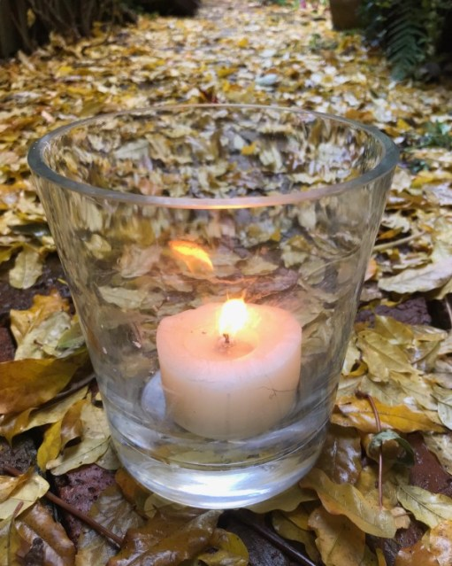A tealight candle in a glass lit for Diddley amongst the autumn leaves on the ground.