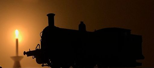 Model steam engine silhouetted in the light of a candle lit for Diddley.