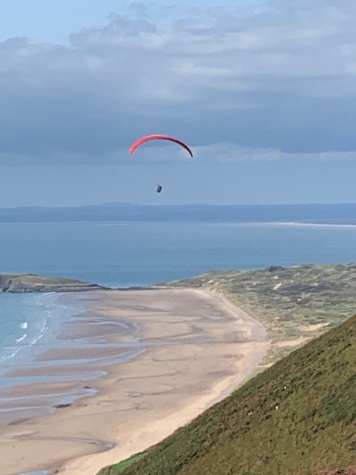 A kitesurfer over Rhossili Down and beach looking north over Llanelli Bay.