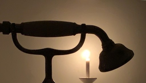 A candle lit for Diddley with the silhouette of an old-fashioned shower head.
