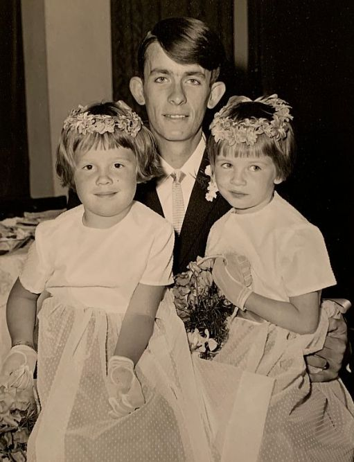 Black & White picture of a man with two young girls dressed as bridesmaids.