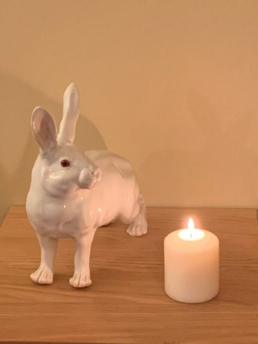 A candle lit for Diddley on the table alongside a white china Hare.