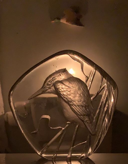 Glass paperweight with an image of a Kingfisher in it, silhouetted against a candle lit for Diddley.