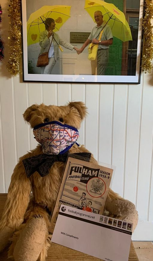 """Bertie wearing an Underground map face mask and showing off the """"riginal Fulham programme for the very first match Bobby ever attended at Craven Cottage"""" book."""