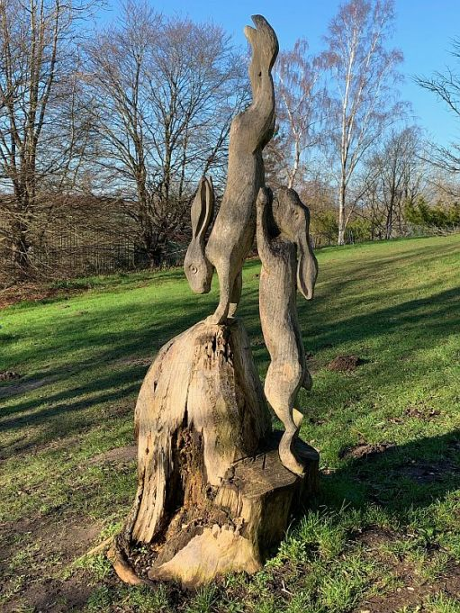 Two rabbits, in an acrobatic pose, carved into a dead tree stump.