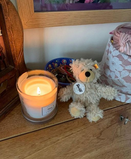 A Candle lit for Diddley with a little Steiff Bear alongsige.