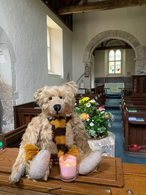 Bertie in Wisley Church with a candle lit for Diddley.